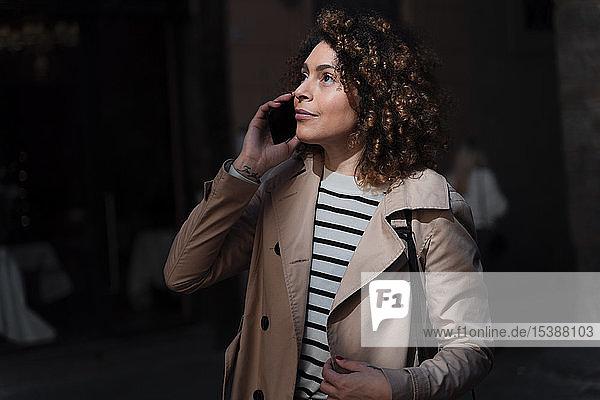 Frau telefoniert mit Handy in einer Gasse