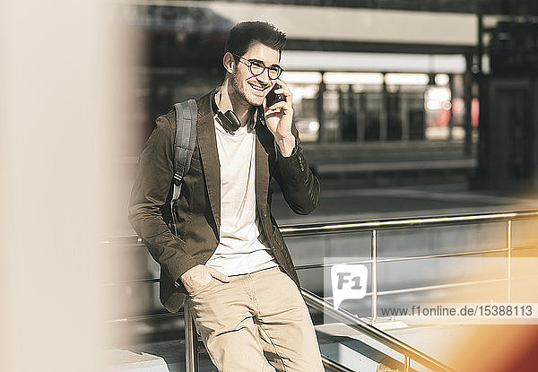 Lächelnder junger Mann  der am Bahnhof mit dem Handy telefoniert