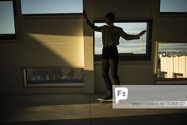 Businesswoman skateboarding at sunset in the office