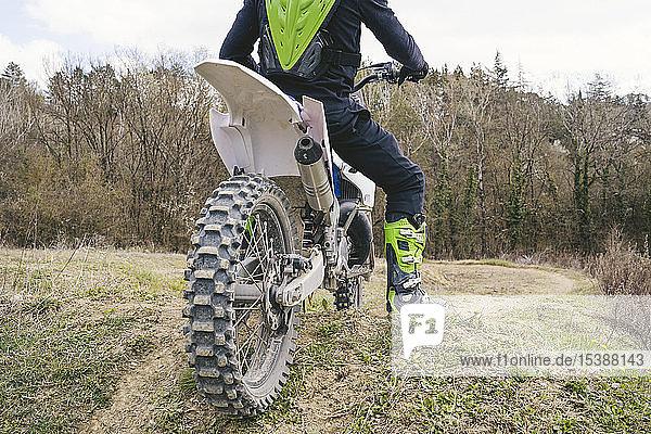 Nahaufnahme eines auf der Rennstrecke stehenden Motocross-Fahrers Nahaufnahme eines auf der Rennstrecke stehenden Motocross-Fahrers