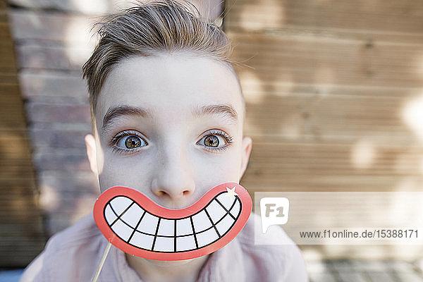 Blonder Junge mit grinsender Mundmaske