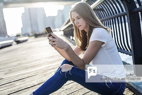 Junge Frau erkundet New York City  macht eine Pause  benutzt ein Smartphone