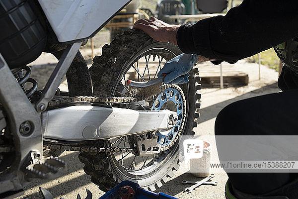 Nahaufnahme eines Mannes  der am Motocross-Bike arbeitet