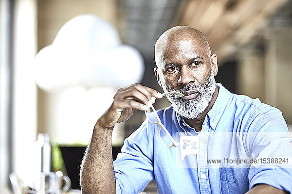 Mature businessman in office thinking with cloud balloon in background