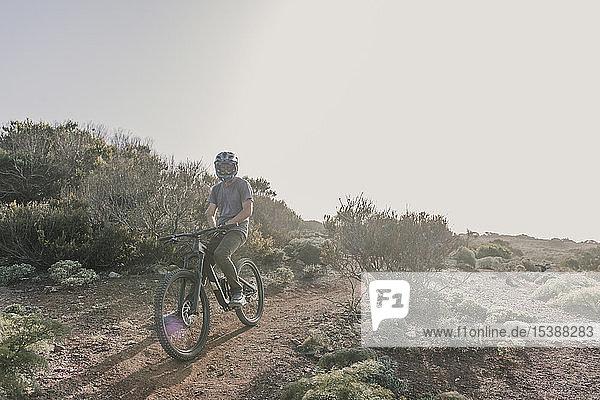 Spain  Lanzarote  mountainbiker on a trip in desertic landscape
