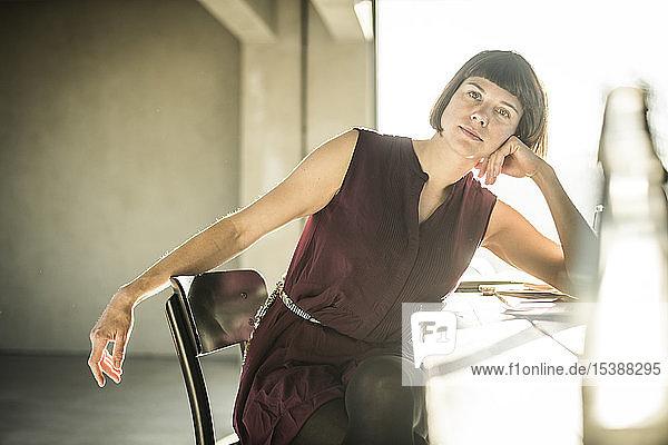 Pensive woman sitting in loft office