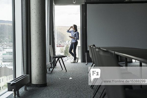 Geschäftsfrau mit Handy steht am Fenster im Büro