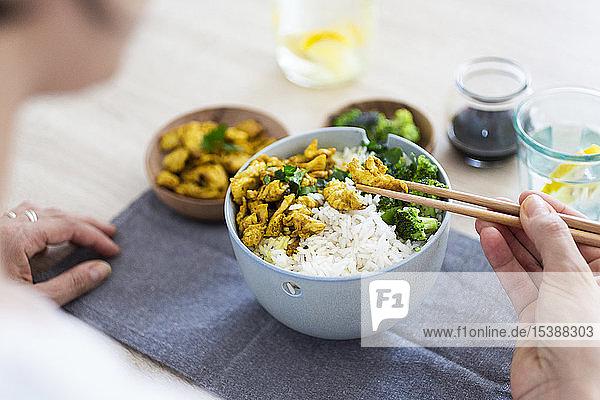 Curry-Huhn  Brokkoli und Reis  Frau mit Stäbchen