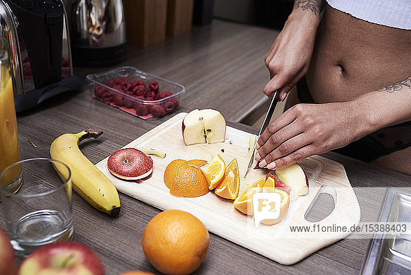 Nahaufnahme einer jungen Frau beim Obstschneiden in der Küche
