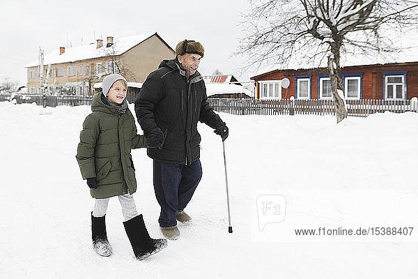 Grossvater und Enkel gehen gemeinsam im Schnee