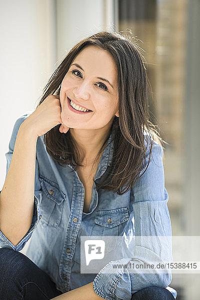 Porträt einer glücklichen Frau  die zu Hause ein Jeanshemd trägt