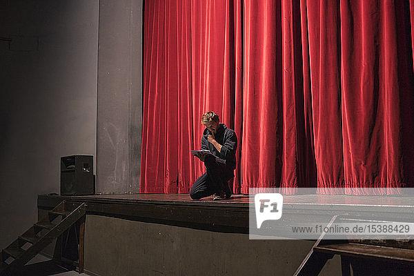 Schauspieler kauert auf der Bühne des Theaters und studiert das Drehbuch Schauspieler kauert auf der Bühne des Theaters und studiert das Drehbuch