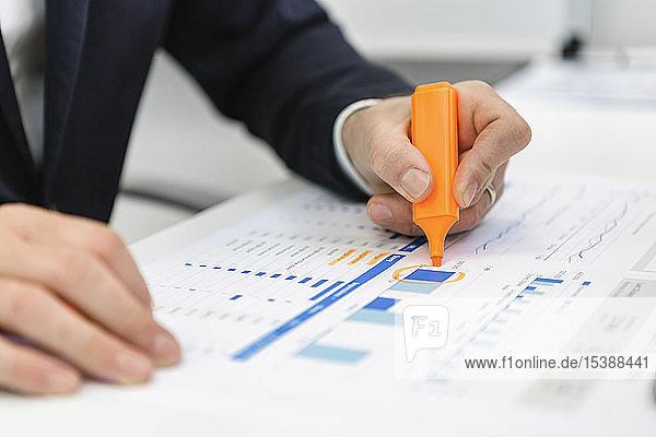 Nahaufnahme eines Geschäftsmannes mit Textmarker auf einem Bericht am Schreibtisch im Büro