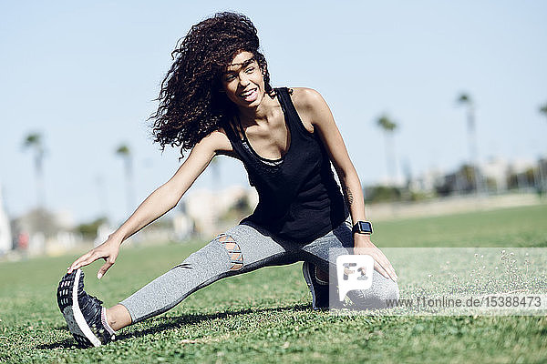 Sporty young woman stretching outdoors