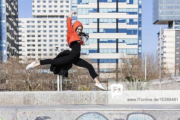 Junge zeitgenössische Tänzerin mit rotem Kapuzen-Shirt  die einen Sprung vorführt