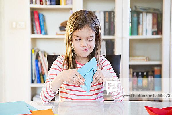 Mädchen bastelt zu Hause an Papier auf dem Tisch