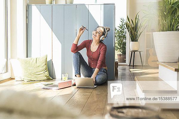 Frau mit Kopfhörern sitzt zu Hause mit Laptop am Fenster