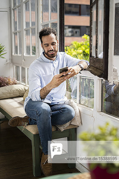 Young man sitting on bench at the window  using smartphone