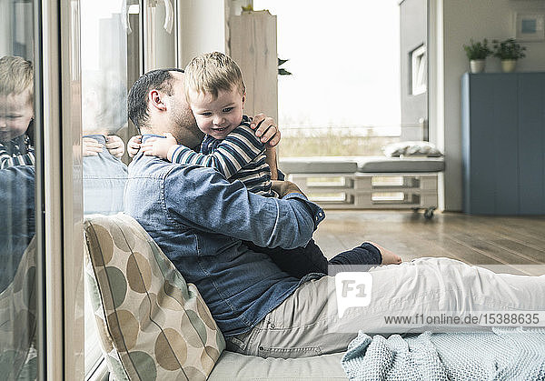 Father cuddling with son at home