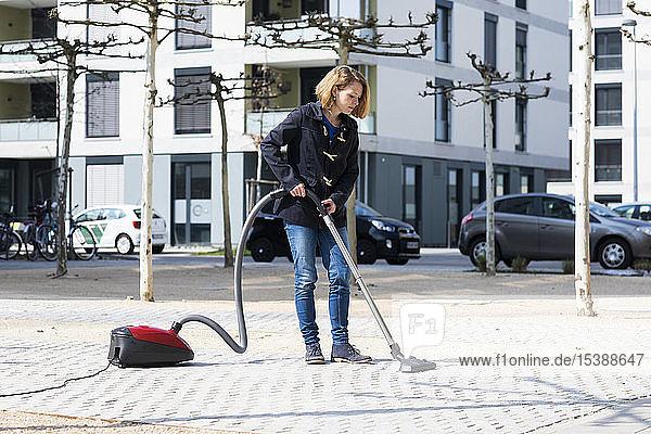 Frau benutzt Staubsauger auf dem Bürgersteig in der Stadt