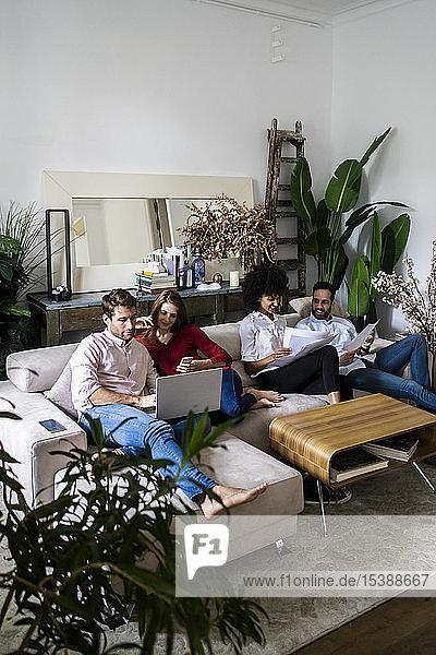 Freunde sitzen auf der Couch  arbeiten zwanglos zusammen  nutzen