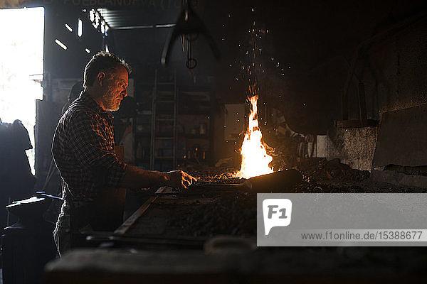 Schmied bei der Arbeit in der Schmiede in seiner Werkstatt
