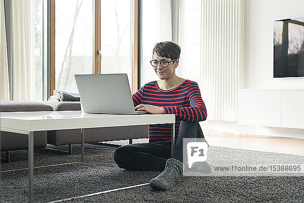 Portrait of woman sitting on the floor of living room using laptop