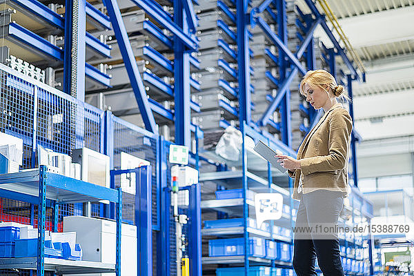 Geschäftsfrau mit Tablette im Fabriklager