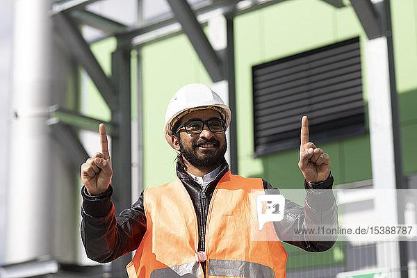 Porträt eines Bauingenieurs vor dem Kraftwerk mit Schutzhelm und Sicherheitsweste