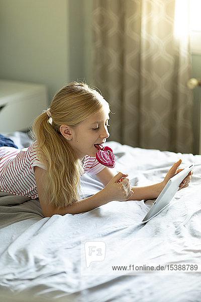 Blondes Mädchen liegt im Bett und leckt Lolli  während sie ein digitales Tablett benutzt