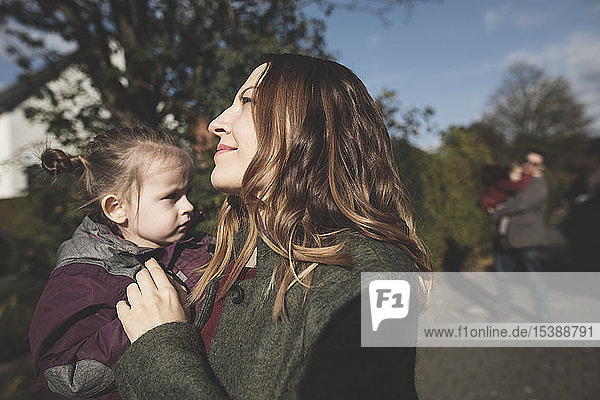 Smiling mother carrying daughter outdoors