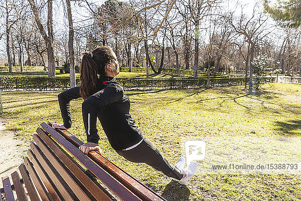 Sporty young woman stretching on park bench