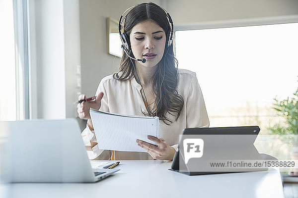Young woman sitting at table at home wearing a headset
