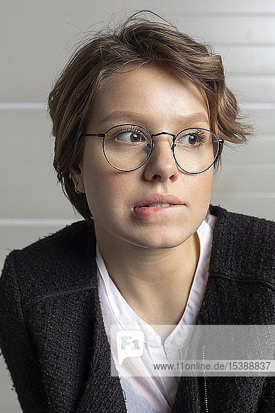 Portrait of young woman biting lip