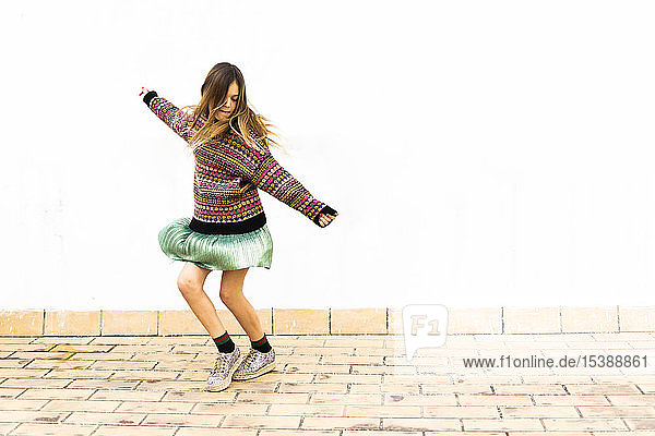 Girl dancing in front of white wall