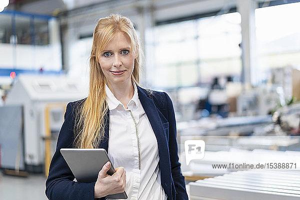 Porträt einer selbstbewussten Geschäftsfrau mit Tablette in der Fabrik