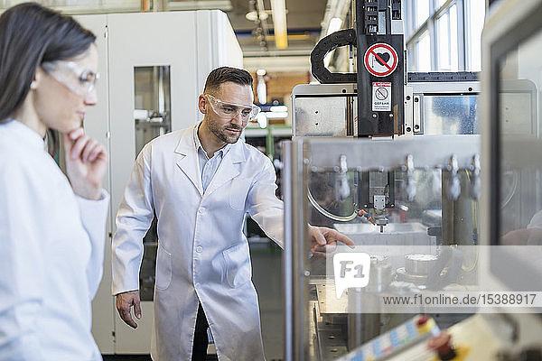 Kollegen in Laborkitteln und mit Schutzbrille beim Blick auf die Maschine in einer modernen Fabrik