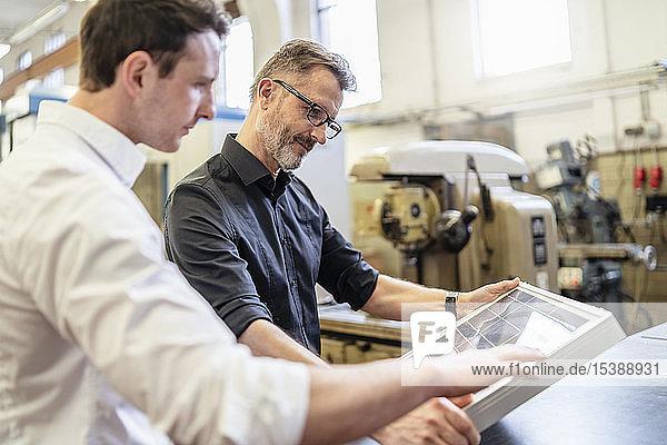Zwei Kollegen in der Fabrik arbeiten an der Solarzelle
