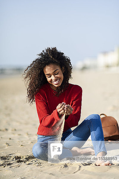 Happy young woman sitting on the beach
