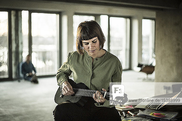 Businesswoman playing the ukulele in office