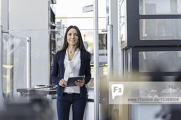 Lächelnde Geschäftsfrau mit Tablette in einer modernen Fabrik