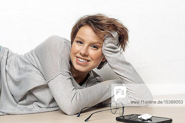 Porträt einer lächelnden jungen Frau auf dem Boden liegend