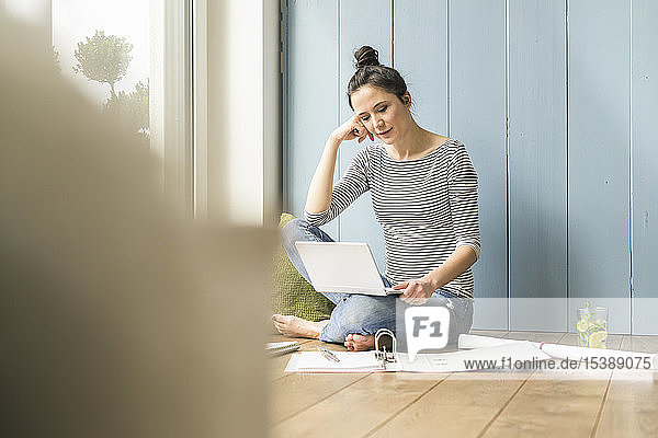 Frau,  die zu Hause am Fenster sitzt und mit Laptop und Dateiordner arbeitet