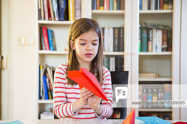 Girl tinkering paper plane on table at home