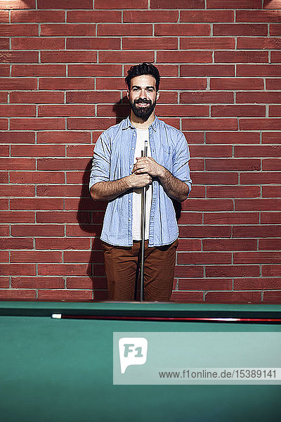 Portrait of smiling man at billiard table