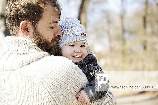 Anhänglicher Vater trägt Tochter im Park