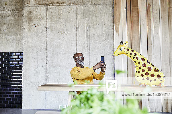 Mature businessman sitting at desk in office with cell phone and giraffe figurine