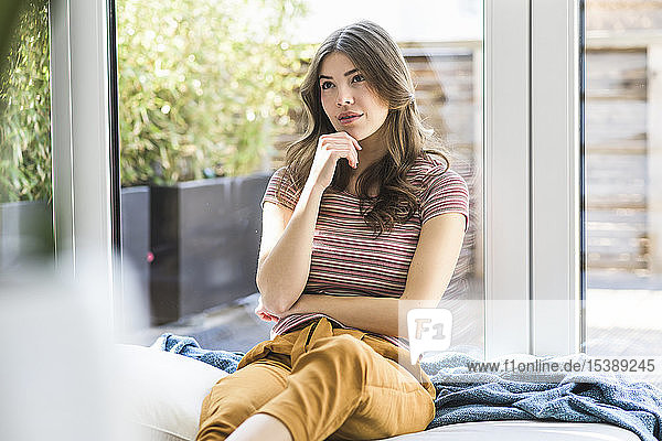 Pensive young woman sitting at the window at home