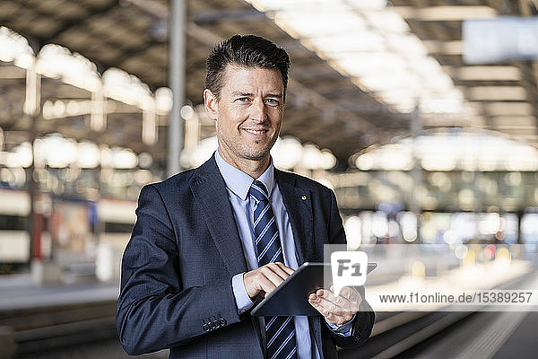 Portrait of smiling businessman using tablet at train station