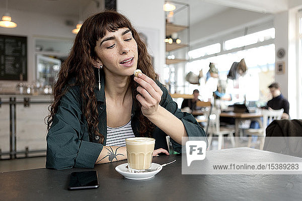 Young woman with milky coffee sitting at table in a cafe